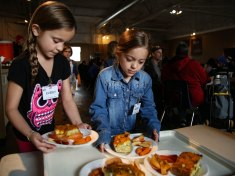 Children of the volunteers at Blood N' Fire serve food to community members on April 14 in Muncie, IN. Plates of food, boxes of pizza and fresh produce were passed out to Muncie locals during the event. Photo by Rebecca Slezak