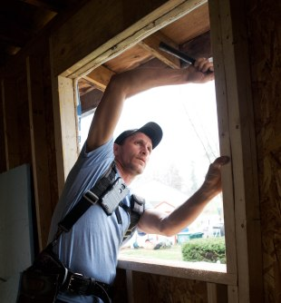 """Jeremiah """"Jay"""" Earehart prepares a wall for window installation at a home he is restoring for Habitat for Humanity in Muncie, Ind. on April 14, 2018. Photo by: Mallory Huxford"""
