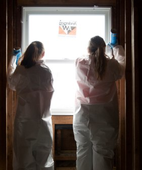 Ball State exercise science students Kiersten Brannon (left) and Katie Smith (right) put insulation into the cracks of a window in Muncie, Ind. as part of their volunteer effort with Habitat for Humanity on April 14, 2018. Photo by: Mallory Huxford