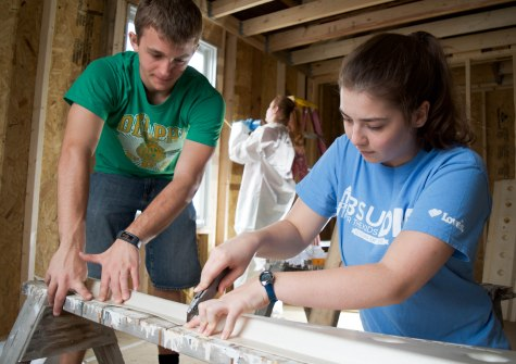 Ball State exercise science students Tanner Pearson (left) and Sarah Maxson (right) cut pieces of foam to be stapled to the ceiling for ventilation as part of their volunteer effort with Habitat for Humanity in Muncie, Ind. on April 14, 2018. Photo by: Mallory Huxford