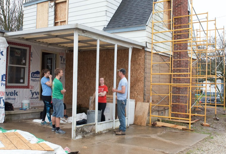 Ball State exercise science students and job site manager Jay Earehart (right) stand under the awning of 1616 South Elm Street in Muncie, Ind. on April 14, 2018. Students are volunteering with Habitat for Humanity to restore this home for a family in need. Photo by: Mallory Huxford