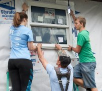 Ball State exercise science students Sarah Marxson (left) and Tanner Pearson (right) work with Habitat for Humanity's job site manager Jay Eareheart to install a window at 1616 South Elm Street in Muncie, Ind. on April 14, 2018. Habitat for Humanity restores homes for people in need and all work is done by volunteers like these students. Photo by: Mallory Huxford