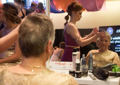 "Rehead salon boutique does guests' hair in the lobby as they wait for dinner and entertainment to start at the Rialzo Charity Gala hosted by Meridian Health Services in Muncie, Ind. on April 14, 2018. Rialzo is Meridian Health Services' annual charity gala celebrating the harmony of ""whole-person"" health."