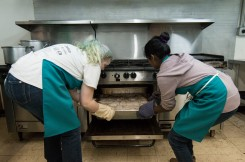 Ball State Senior Landscape Architecture major Virginia Jenkins(left) and (right) Urban Planning Graduate Student Varu Musumuri, pulls out a large pan of chicken and potatoes to serve to the Avondale community for Thursday night commune dinner. Jenkins directed the team of students and volunteers as she provided all the recipes served at the dinner, ÒThey are just in my headÉ all from try and fail.Ó said Jenkins. Grace Hollars, DN