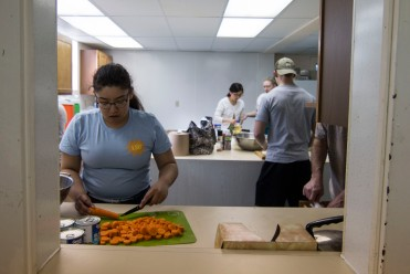 Ball State Senior Architect major, Ashley Caceres carefully cuts carrots while the rest of the students and volunteers grate cheese, cut melons, and line pans with chicken and rice for Thursday night commune dinner, April 12, at Avondale United Methodist Church. Grace Hollars, NPPA