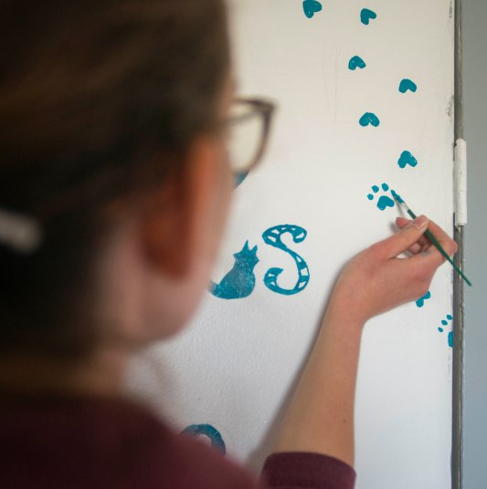 Lydia Volpe, a sophomore animation major, paints paw prints on one of the doors in one of the free roam cat rooms on April 13 at ARF. Volpe heard ARF used a stencil to paint paw prints and decided she could volunteer her time to paint some for ARF. Breanna Daugherty | SFG