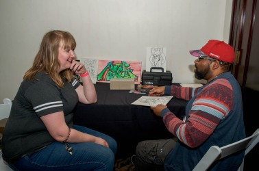 Leon Crosby (right) creates a caricature of Olivia Willard (left) at Cornerstone Center for the Arts' annual Brewfest celebration on April 13, 2019.