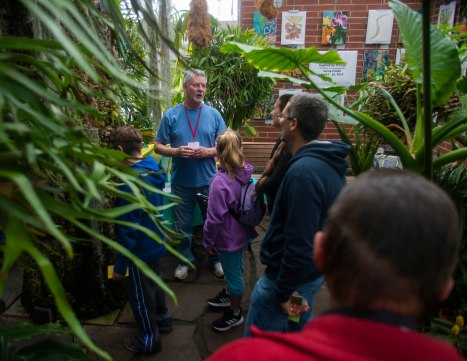 Tom Schwartz, a greenhouse docent, gives a tour to guests on April 13 in the Rinard Orchid Greenhouse on Ball State's campus. The greenhouse features over 2,000 orchids and it contains the largest university-based orchid collection in the United States. Breanna Daugherty | SFG