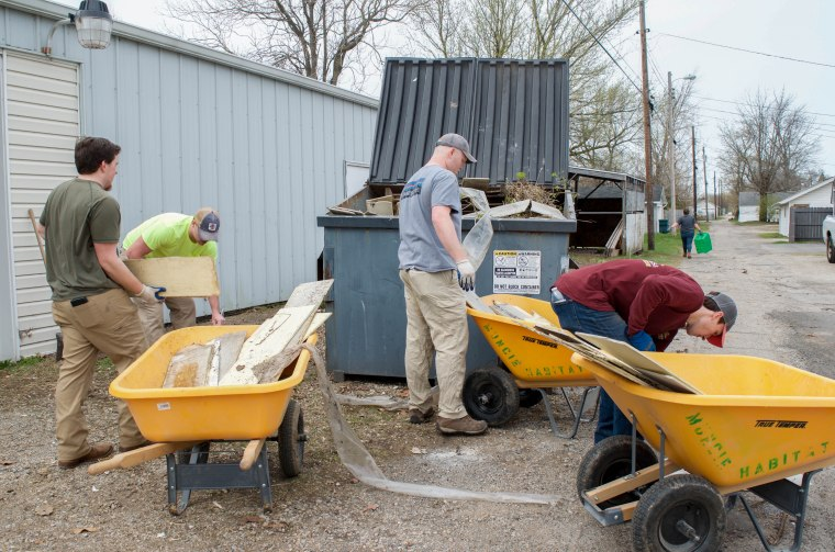 Volunteers from Ball State's construction management program work on cleaning up the area around Habitat for Humanity's Muncie headquarters at 1923 South Hoyt Avenue on April 13, 2018.