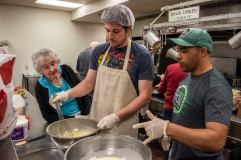 Aaron Thompson, right helps Tyler Stricklin and Faye Buchanan with the Tres Leches cake by telling them what the next step is. Muncie Mission volunteers help prep and serve food to the locals in Muncie.