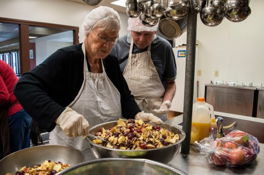 A few volunteers from Muncie help prep and serve food at Muncie Mission, Sat. April 13. Tony Parks, left, stands by his wife Rebecca Parks, while she mixes the fruit with a sweet dressing.