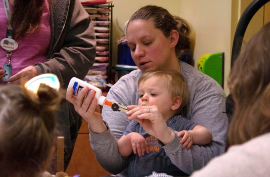 Katey O'Connor holds her friend's child Michael Clerget at a volunteer reading at the Kennedy Library in Munice, Indiana on April 12,2019. Jack Hart