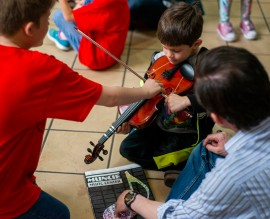 A member of the Youth Symphony Orchestra of East Central Indiana shows his brother how to play the violin after performing on April 13 at the Muncie Mall. The Youth Symphony Orchestra of East Central Indiana performed their Muncie Outreach Concert to help recruit individuals for the next year. Breanna Daugherty | SFG