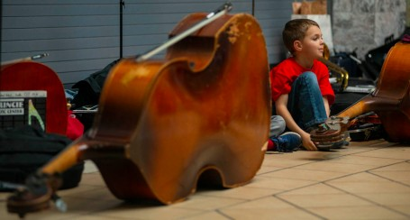 A member of the Youth Symphony Orchestra of East Central Indiana sits near a cello and listens to one of the levels perform on April 13 at Muncie Mall. The orchestra looks to develop the musical talent and nurture the personal growth of young people in Muncie and East Central Indiana. Breanna Daugherty | SFG