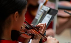 A member of the Youth Symphony Orchestra of East Central Indiana plays the violin during their April 13 performance in the Muncie Mall. Breanna Daugherty | SFG