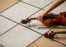 A member of the Youth Symphony Orchestra of East Central Indiana picks up her violin before the final song of the Muncie Outreach Concert on April 13 at the Muncie Mall. Breanna Daugherty | SFG