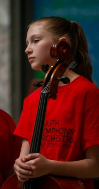 A member of the Youth Symphony Orchestra of East Central Indiana cradles her cello as she listens to other members perform during the Muncie Outreach concert April 13 at the Muncie Mall. Breanna Daugherty | SFG